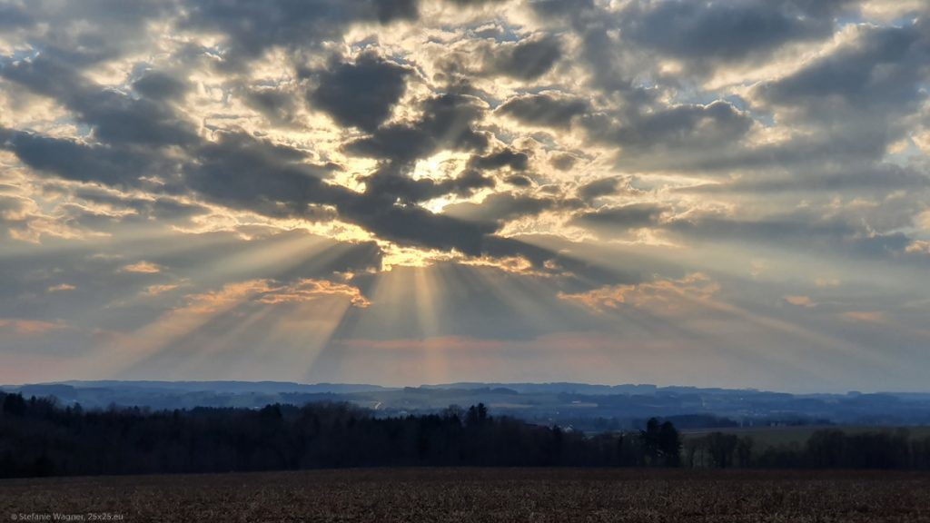Sunset behind clouds spreading rays of light