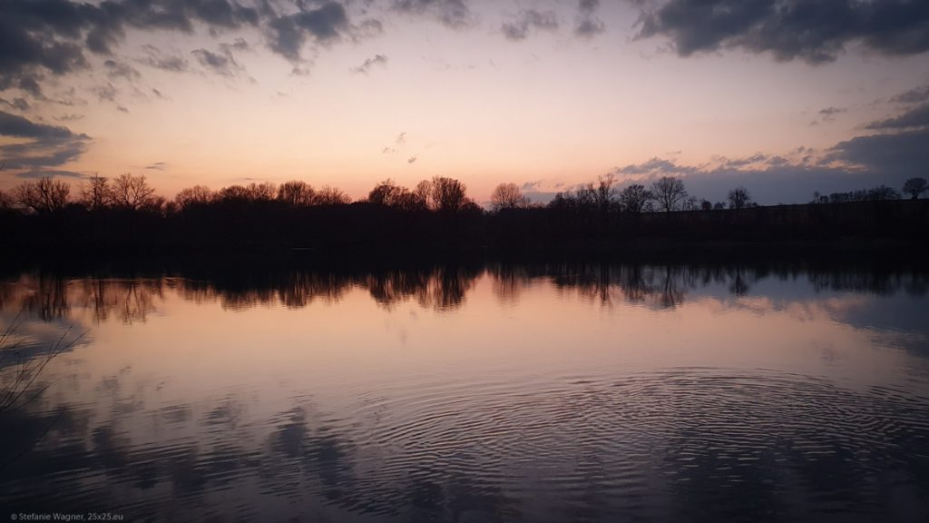 After the sunset, red sky, silhouette of trees on the other side of the river, everything mirrored on the surface